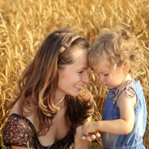 Woman with child in field of wheat